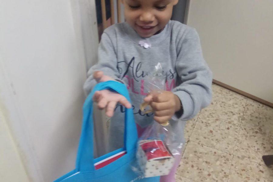ילדה שמחה עם המתנה החדשה במעון אמונה חדרה